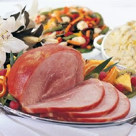 Sliced baked ham alongside bowls of pasta and vegetables