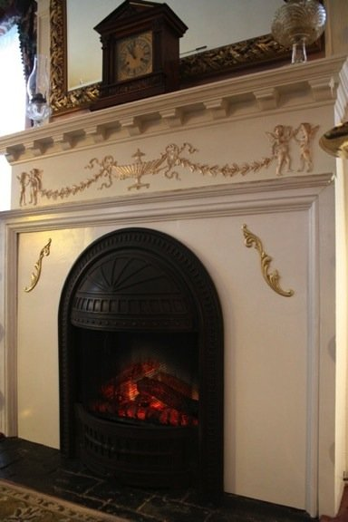 The Inn's beautiful white and gold painted wraparound mantel with arched fireplace