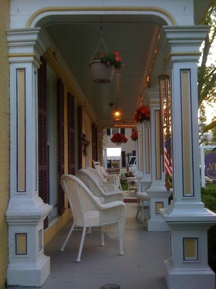 Side view of the covered front porch with white wicker chairs and hanging baskets with red flowers