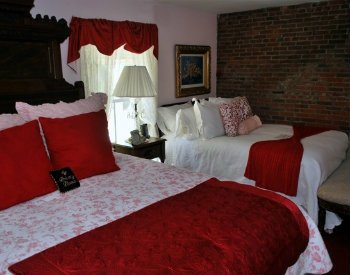 Prince Alfred guest room with two beds, one with red bedding and the other with white and a window