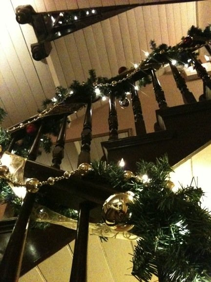 The Inn's stairway railing wrapped with green garland and white twinkle lights