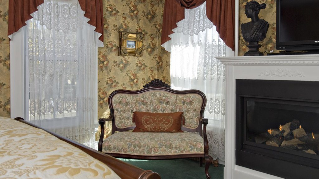Elegant gues troom with gold floral wallpaper, windows, settee and fireplace