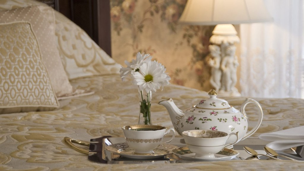 Guest bed with silver platter topped with beautiful ivory and gold teapot, cups and saucers