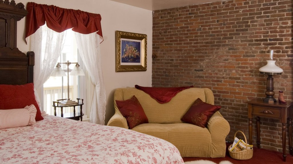 Guest room with brick wall, corner gold sofa, window with sheers, and carved wood bed with red and white bedding
