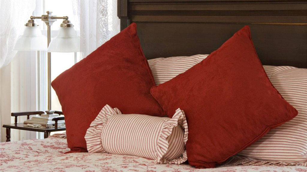 Close-up view of guest room bed, wood carved headboard, white bedding with red flowers, and red pillows