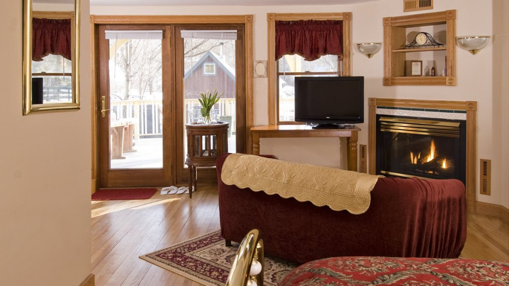 Spacious guest room with wood floors, beige walls, corner fireplace, red sofa, and lots of natural light