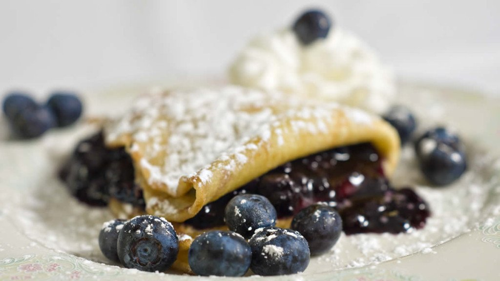 Breakfast crêpe filled with fresh blueberries and topped with powdered sugar