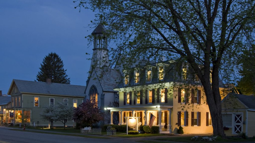 The Inn's exterior at dusk with all of the lights on inside surrounded by the silhouettes of trees
