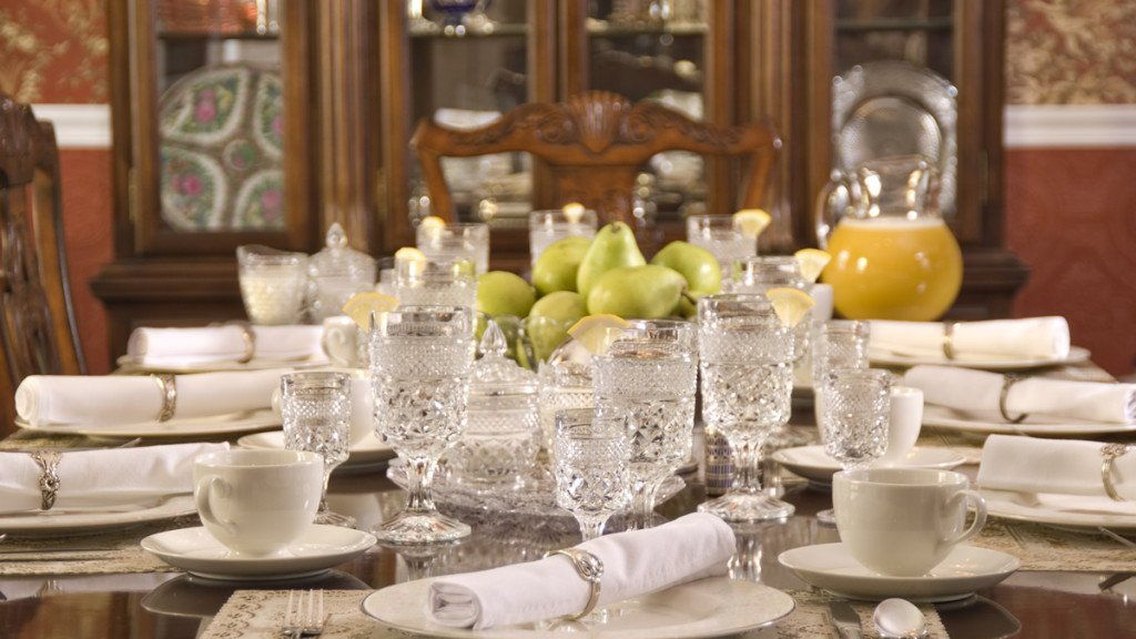 Elegant dining table setting with white china and crystal glassware