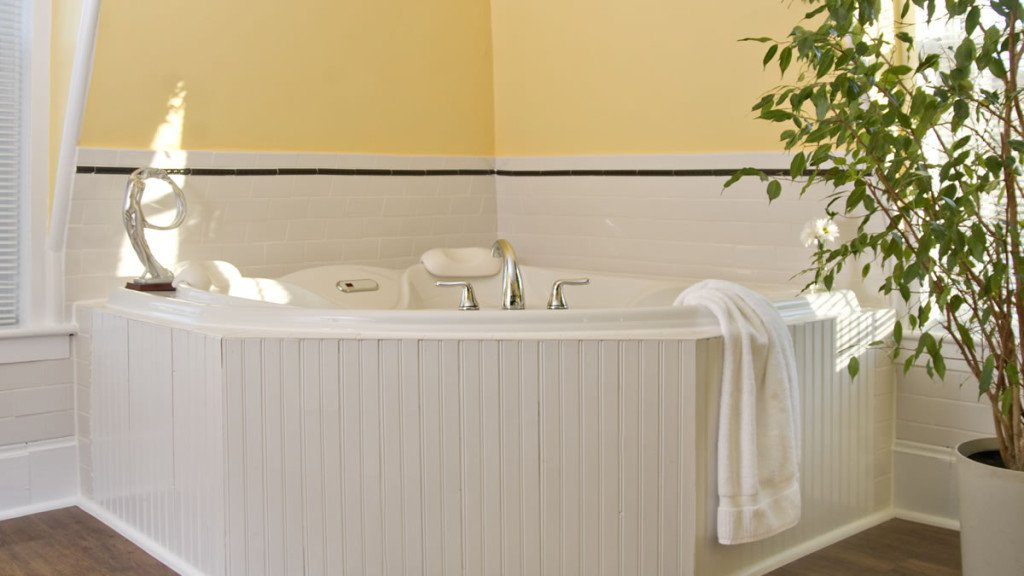 Corner guest room tub with beadboard exterior and yellow walls