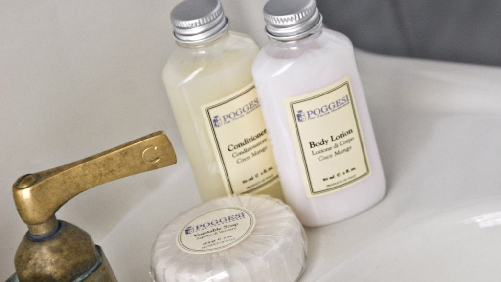 Close-up view of white guest bath sink with two toiletry bottles and wrapped soap