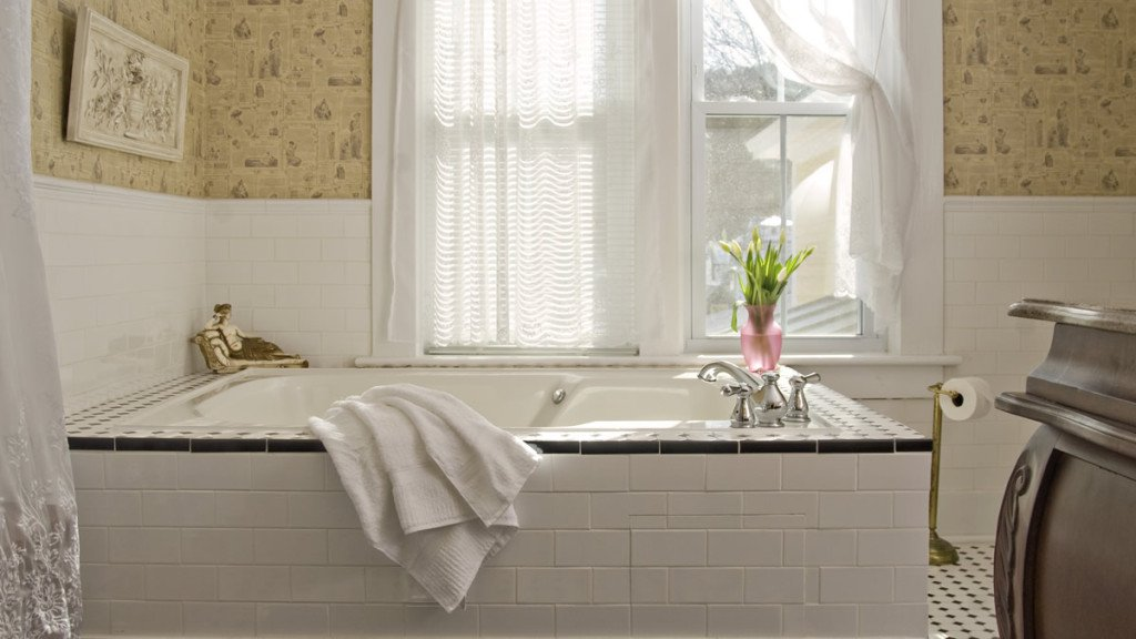 Guest bath tub surrounded by white tile in front of a double window with white sheer curtains