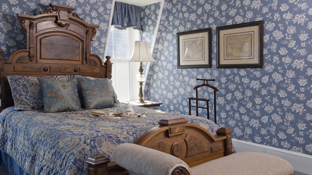 Guest room with blue and white wallpaper, carved wood bed, blue and white bedding and bench at the foot of the bed