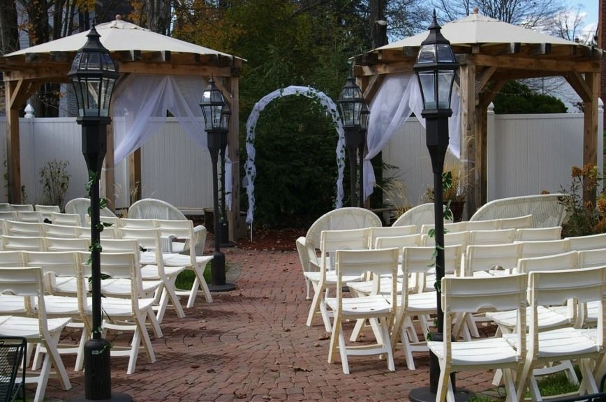 Outdoor garden wedding with two sections of rows of white chairs, an arched pergola and brick aisle