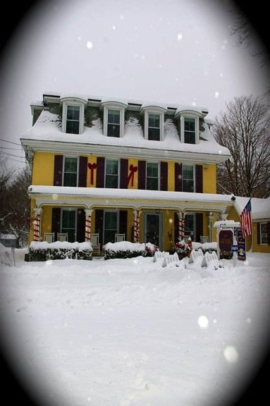 The Inn's exterior during Christmas time, yellow siding, twinkle lights on the porch posts, and snow covered ground
