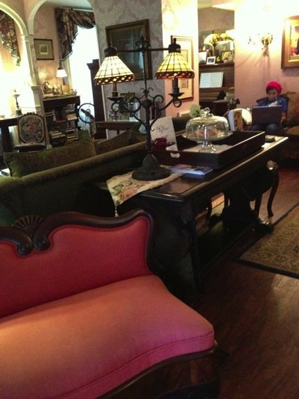 The elegant parlor with dark wood furniture, red settee and Tiffany-style lamps