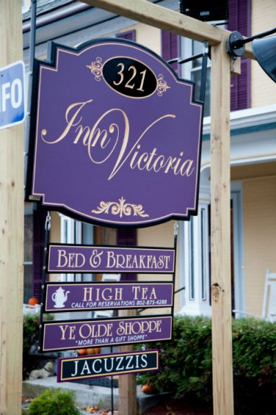 Up close view of the Inn's exterior hanging sign, purple with gold lettering: Inn Victoria Bed & Breakfast