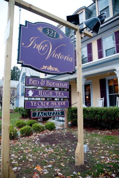 Inn's exterior sign hanging sign, purple with gold lettering: Inn Victoria Bed & Breakfast, High Tea, Ye Olde Shop, Jacuzi