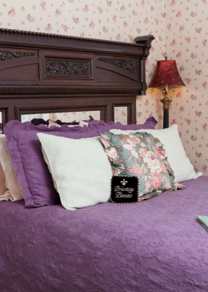Guest bed with carved wood headboard, purple bedding and white and floral pillows