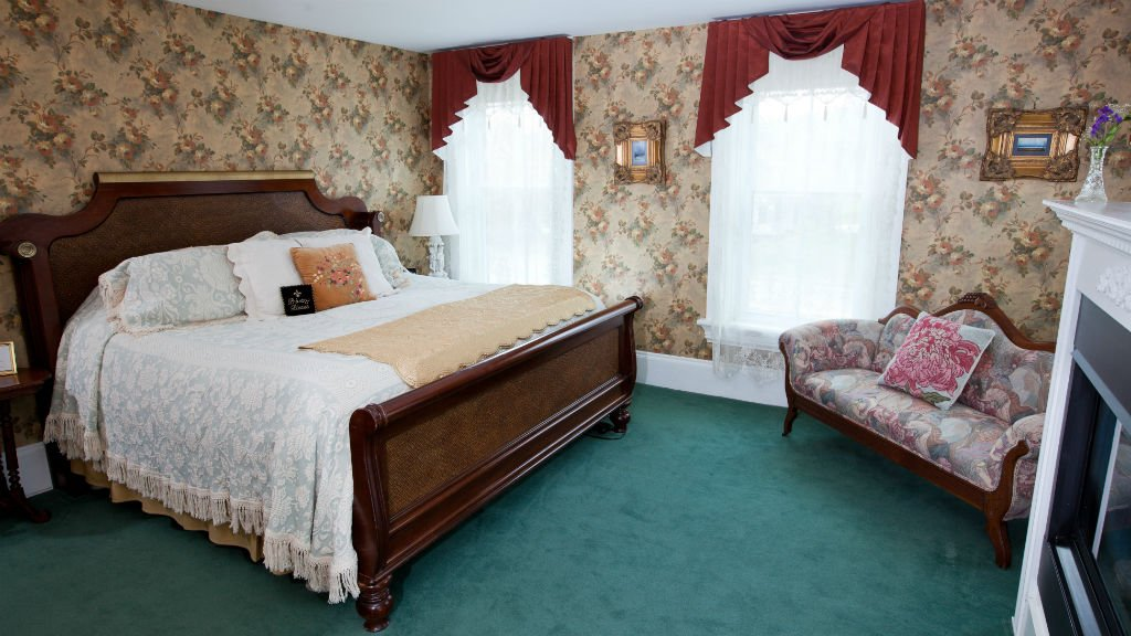 Guest room with two windows with sheers, wood bed with ivory bedding and corner settee