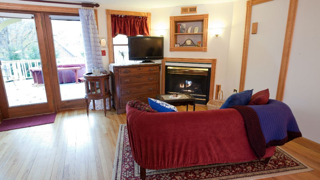 Spacious guest room with wood floor, corner fireplace, sofa, sliding doors and TV
