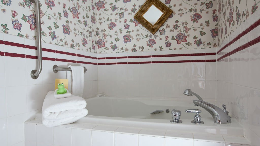 Guest bath tub with white tile floral papered walls, and white towels