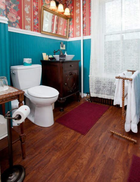 Guest bath with turquoise walls, wood floor, sheer lace curtains and white towels