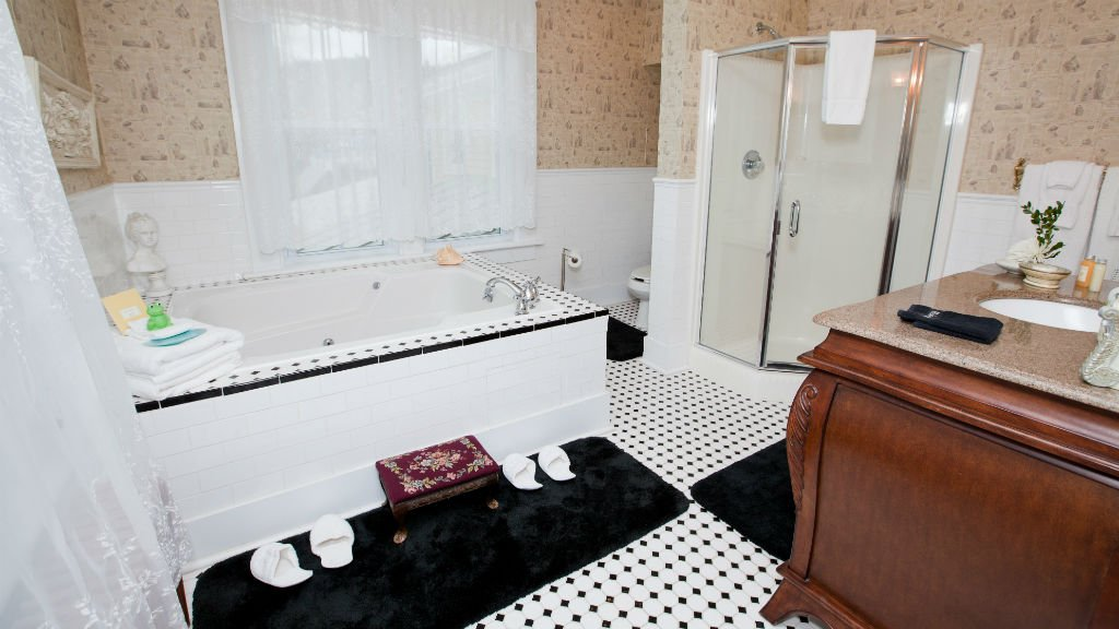Guest bath with beige papered walls, white tiled tub, black and white tiled floor and antique vanity with sink