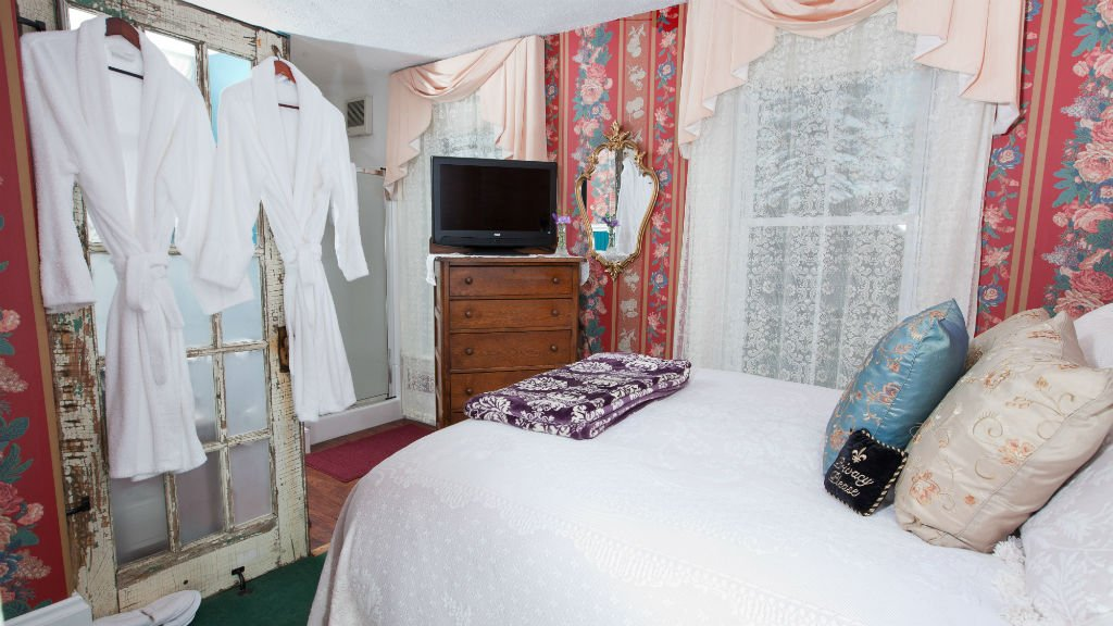 Cozy guest room with red floral walls, white bedding, sheer curtains and two white terry cloth robes