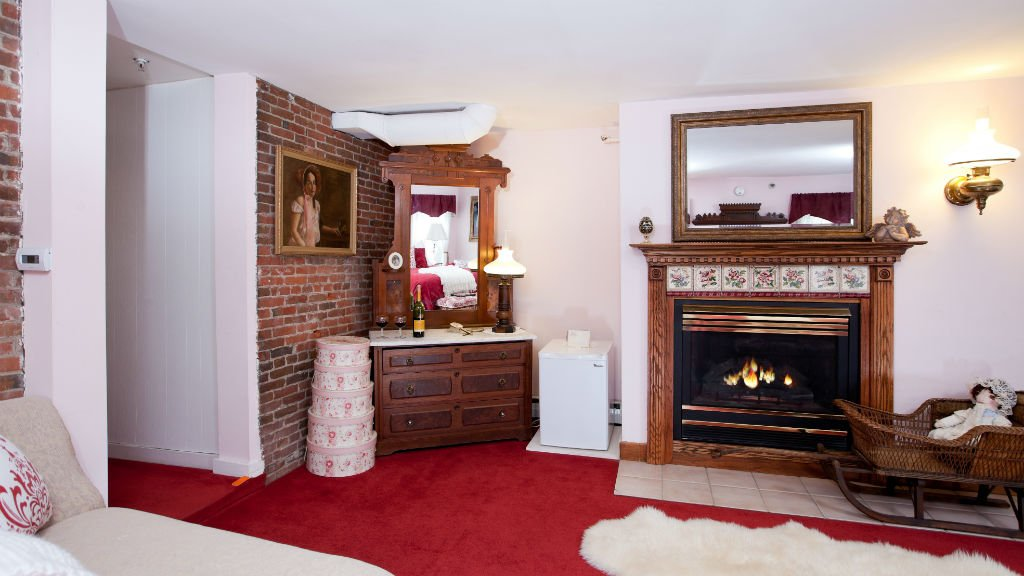 Guest room with red carpeting, fireplace with mirror, and corner antique dresser with mirror