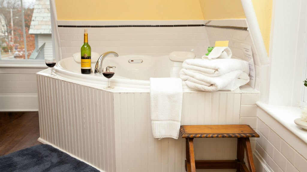 Corner guest bath tub with beadboard front, yellow walls, and two windows