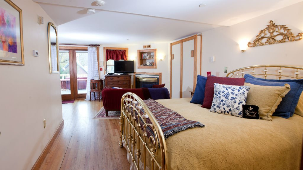 Spacious guest room with wood floor, yellow bedding, sitting area with fireplace and sliding doors