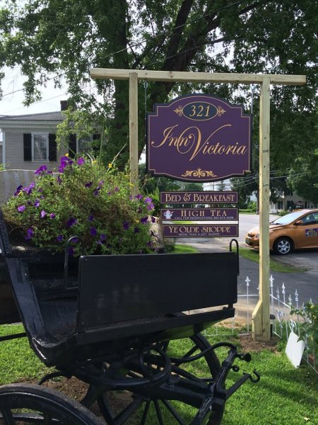 The Inn's exterior sign, purple with gold letter that says Inn Victoria Bed & Breakfast