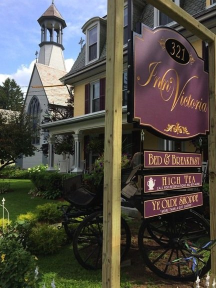 The Inn's exterior sign, purple with gold letter that says Inn Victoria Bed & Breakfastm