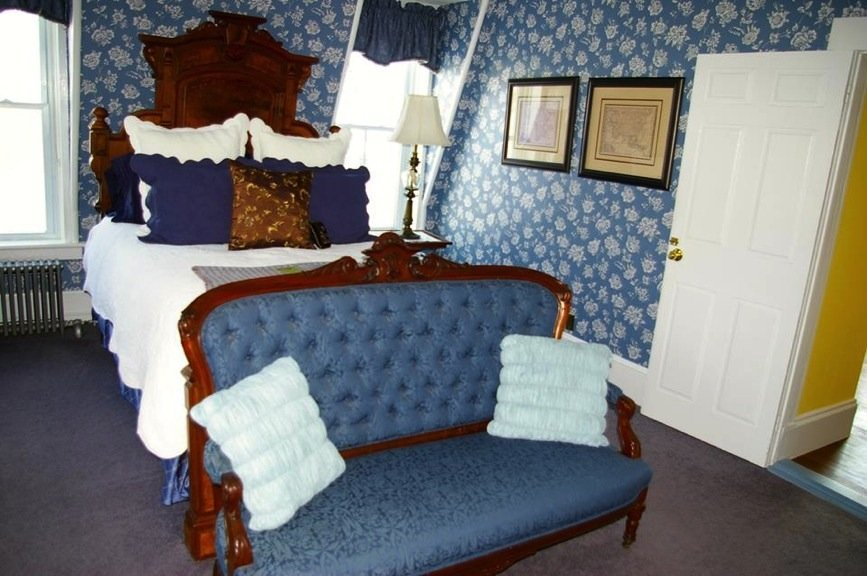 Victoria guest room with blue and white papered walls, white bedding, windows and blue settee