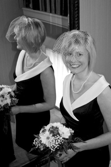 Bride wearing a black and white dress and white pearls holding a bouquet and smiling