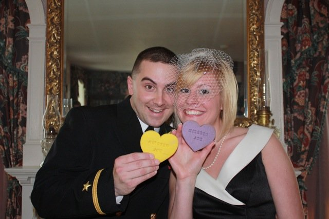 Bride and groom leaning in together holding colorful heart-shaped cookies and smiling inside the inn
