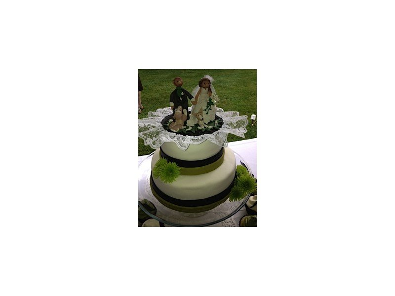 Two-tiered wedding cake with bride and groom cake topper