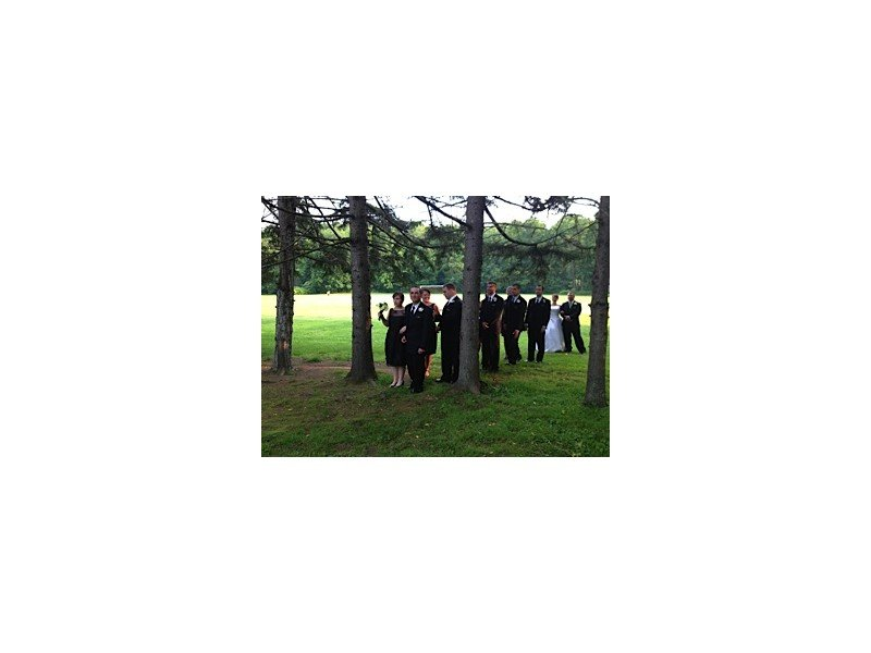 Wedding bridal party standing outside among the trees getting ready to walk