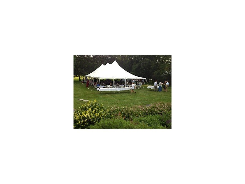 View from afar of the white wedding tent surrounded by lush green landscaping