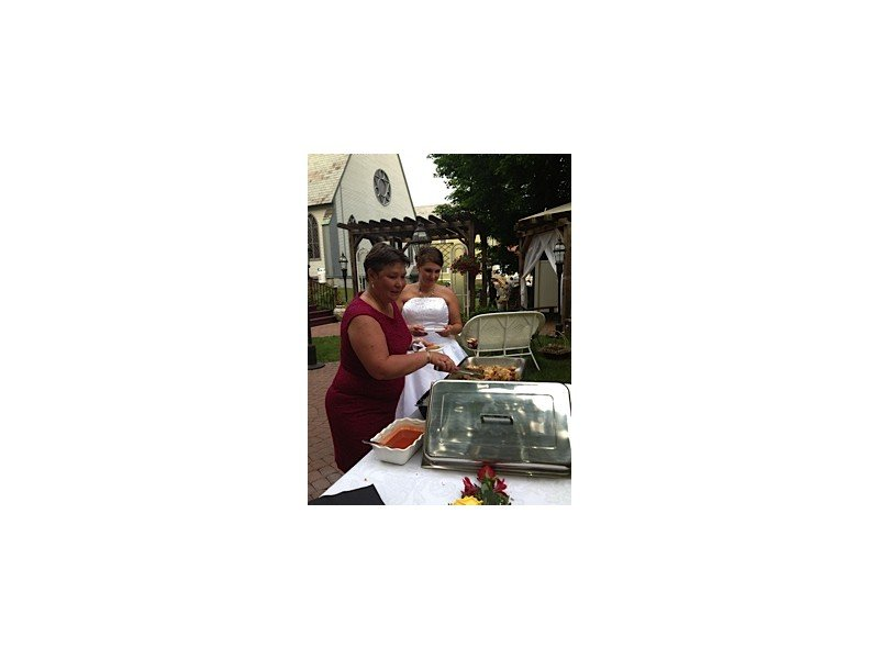 A bride and bridesmaid standing outside at the foot table