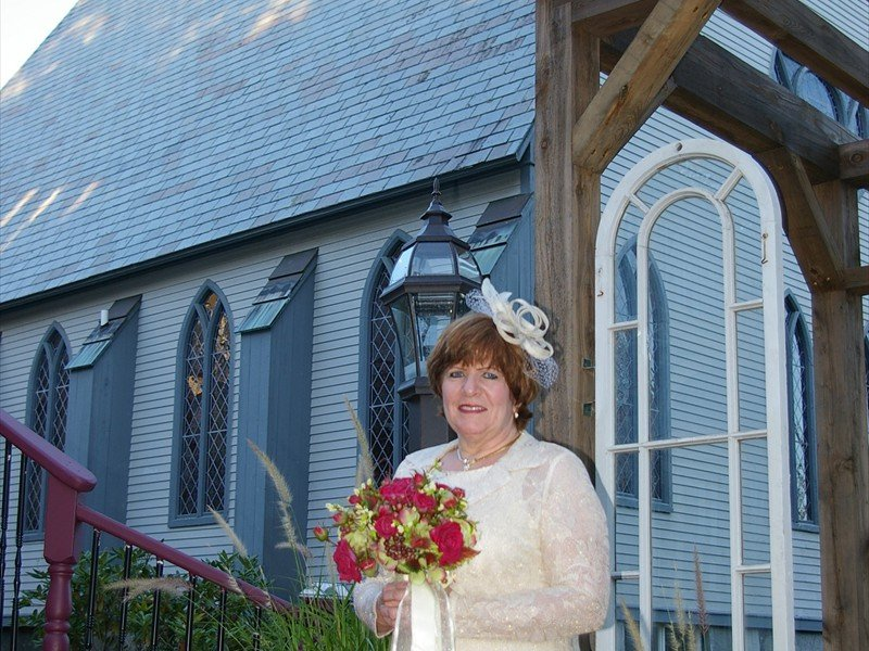A bride standing outside a church holding a red and green bouquet