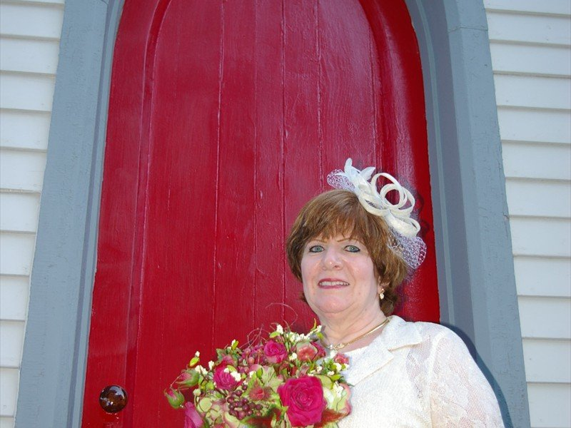 Bride standing outside the red door of the church holding a bouquet