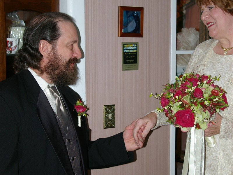 Groom kneeling down holding the bride's hand as she holds a bouquet with red flowers