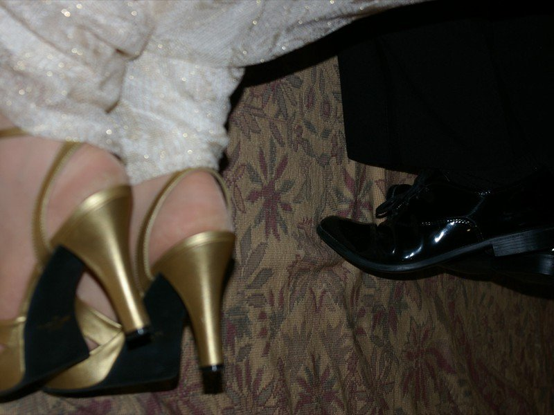 The bride and grooms feet, black shiny shoes and gold high heels