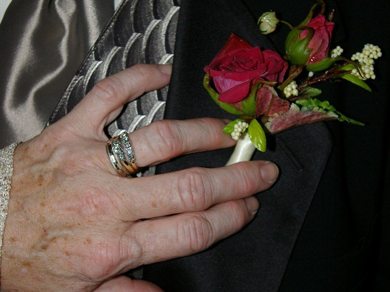 The brides hand with her wedding rings on the grooms jacket next to a red boutonniere