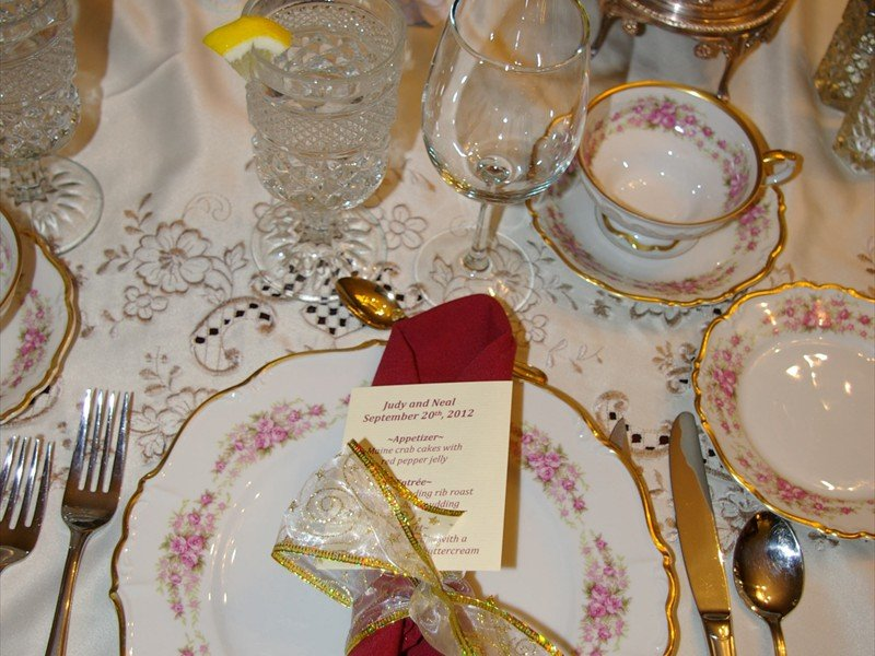 Wedding table set with lace ivory cloth, china, red napkins with gold holders and crystal glasses