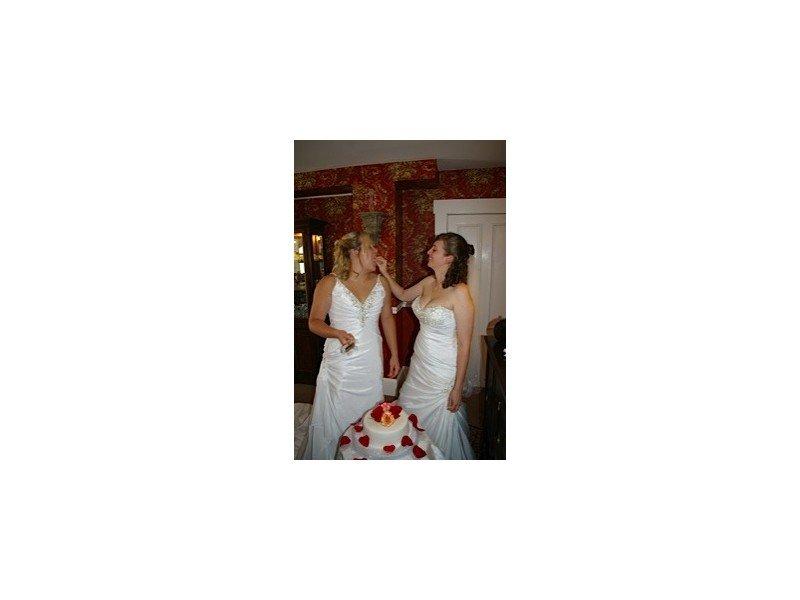 Two brides sharing cake
