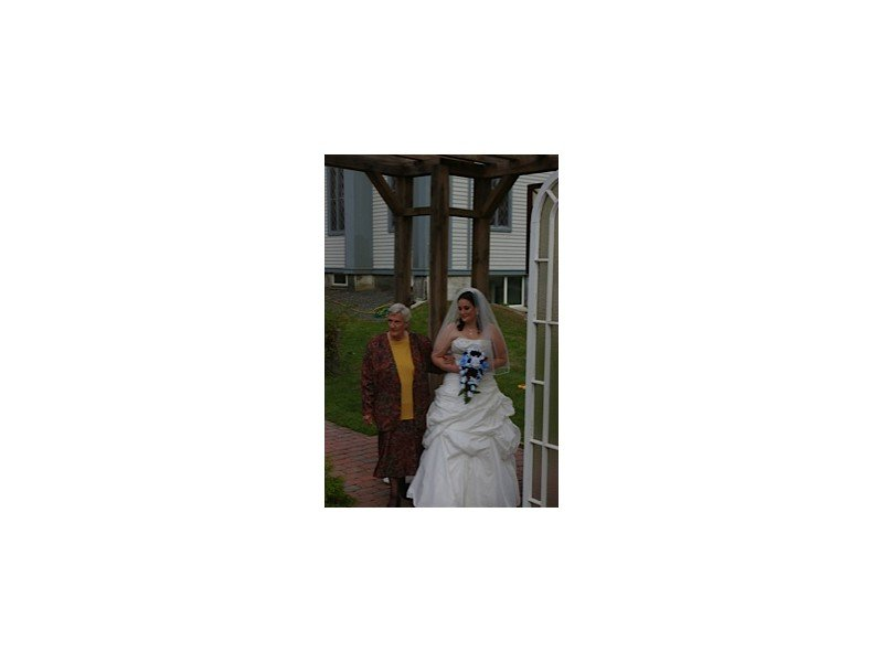 Bride and her mom walking under the outdoor wooden pergola