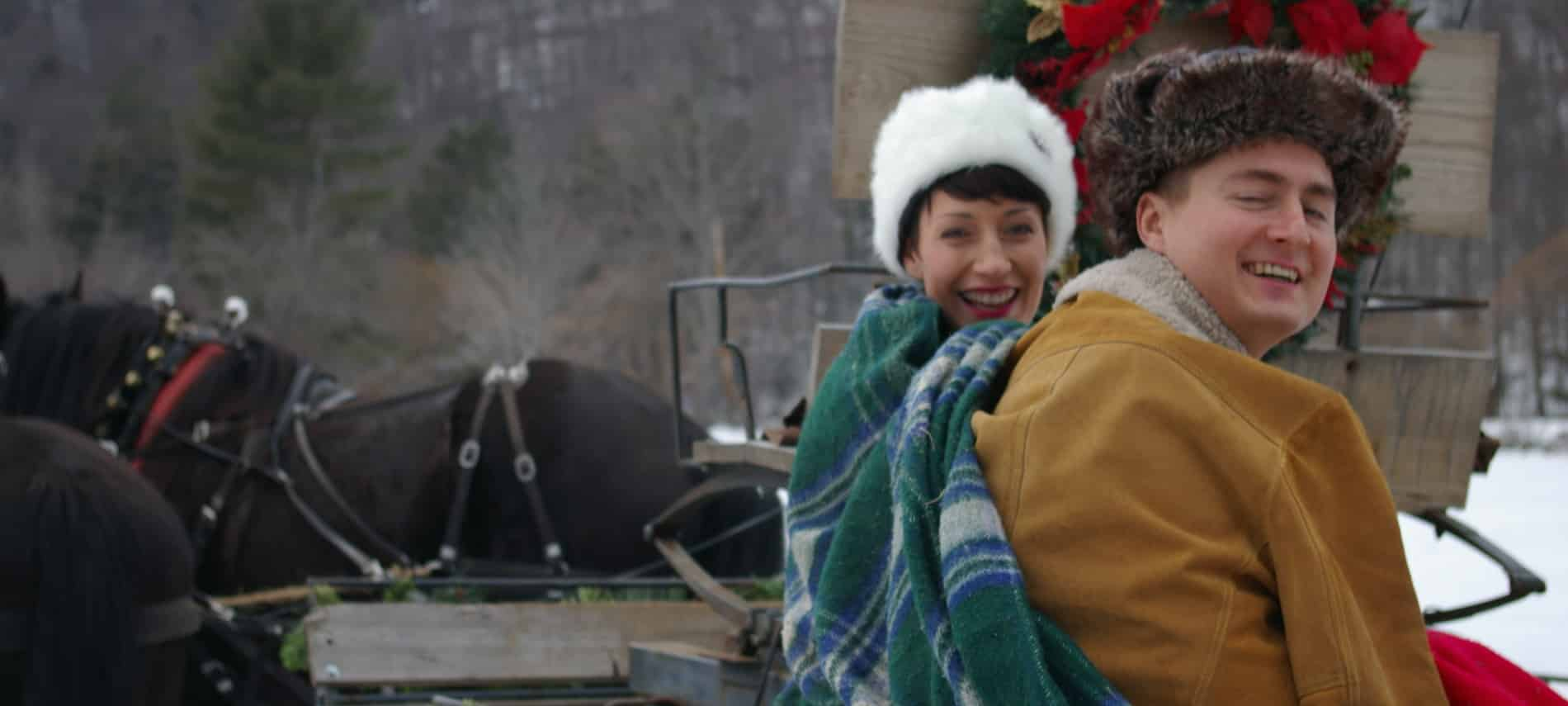 Man and woman wearing winter coats, hats and blankets sitting on a horse-drawn sleigh